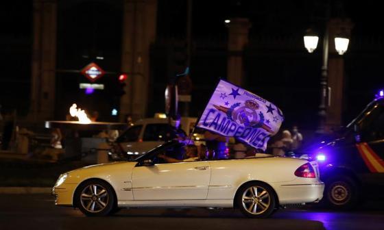 Un aficionado festejando desde su auto con la bandera del Real Madrid.