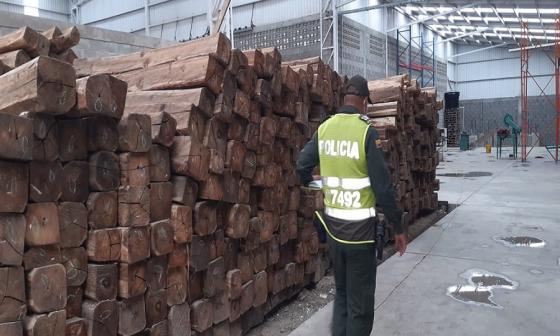 Un policía inspecciona la madera durante el decomiso.
