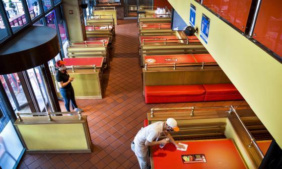 Un trabajador limpia las mesas de un restaurante que se prepara para la reapertura.