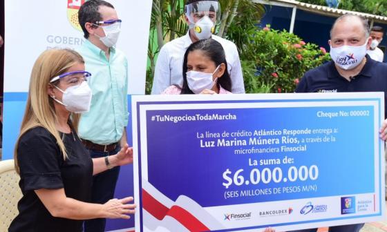 La gobernadora Elsa Noguera entrega el cheque a Luz Marina Múnera.