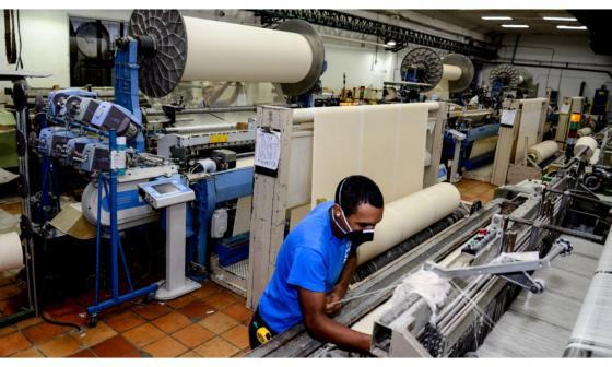 Un trabajador de una compañía del sector textil opera una de las máquinas.