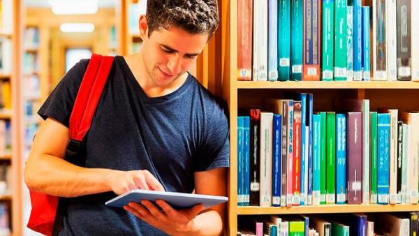 Un estudiante lee en su tableta un escrito.