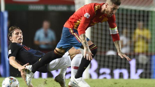 Luka Modric, de Croacia, despoja del balón a su compañero en el Real Madrid, Sergio Ramos, de España.