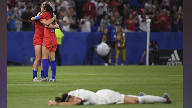 Dos jugadoras de la Selección de Estados Unidos se abrazan tras derrotar 2-1 a Inglaterra y pasar a la final del Mundial, mientras que una rival llora sobre el césped del estadio.