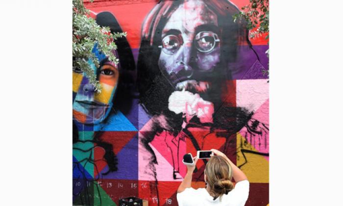 Una mujer toma una foto del mural del artista brasileño Kobra con la imagen de Yoko Ono y John Lennon, en el distrito Wynwood.
