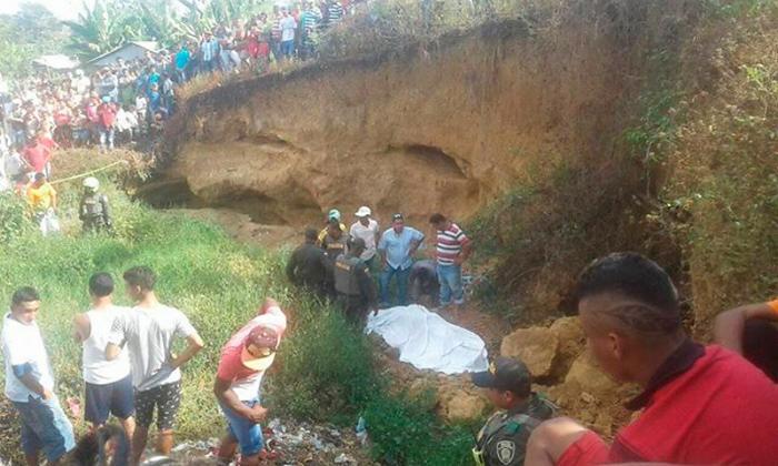Familiares y curiosos observan el cuerpo de la única víctima del alud de tierra que cayó sobre varios jóvenes en El Carmen de Bolívar.