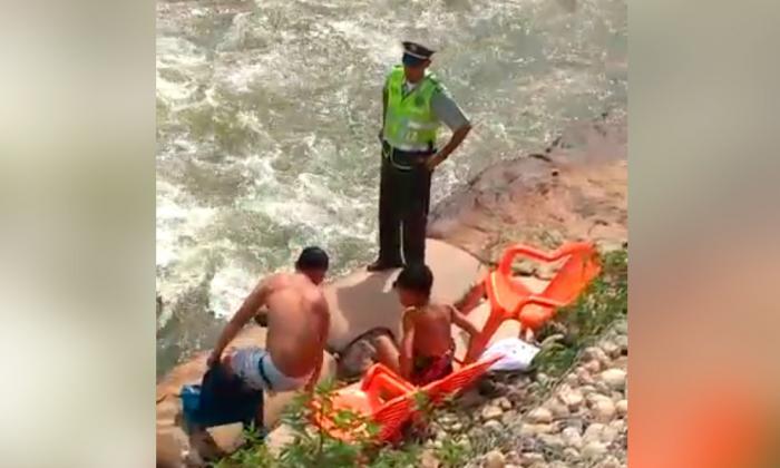 La pareja se viste frente al policía quien les impone la multa.