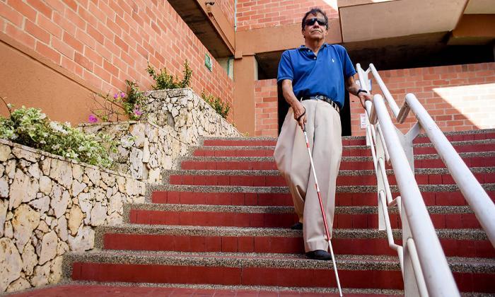 José baja una de las escaleras del conjunto donde vive. Este es uno de los obstáculos que enfrenta a diario.
