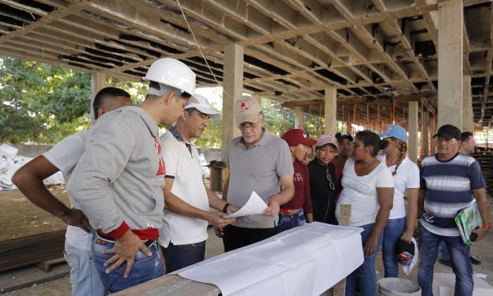 El gobernador inspecciona los planos de la obra.