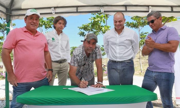 El alcalde Char firma el convenio. Lo observan el director de la ADI, Alberto Salah; el director del AMB, Libardo García, y dos ejecutores del programa.