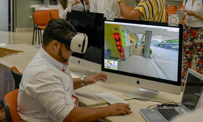 Un  estudiante del Sena a través de gafas de realidad virtual observa el proyecto informático que se presentó durante el lanzamiento del programa de transformación digital.
