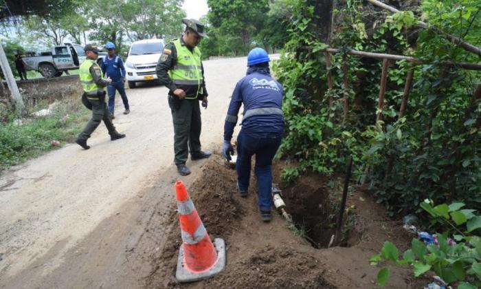 Un operario de Triple A retira una conexión ilegal. En la operación la acompaña la Policía.