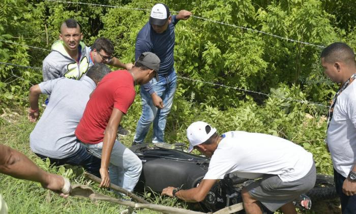 Personas se acercaron para sacar la moto y ayudar a los heridos.