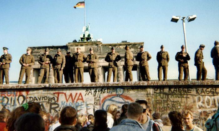 En esta foto de archivo tomada el 11 de noviembre de 1989, los guardias fronterizos de Alemania Oriental se paran en una sección del muro de Berlín con la puerta de Brandenburgo al fondo en Berlín.