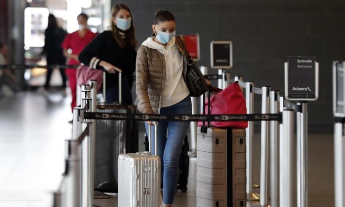 Viajeros usan máscaras en el aeropuerto El Dorado en Bogotá.