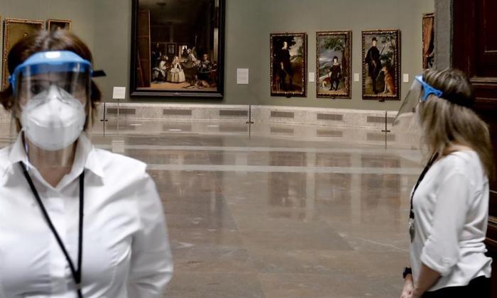 Dos empleadas del Museo del Prado con máscarillas y pantallas protectoras durante la presentación de Reencuentro.