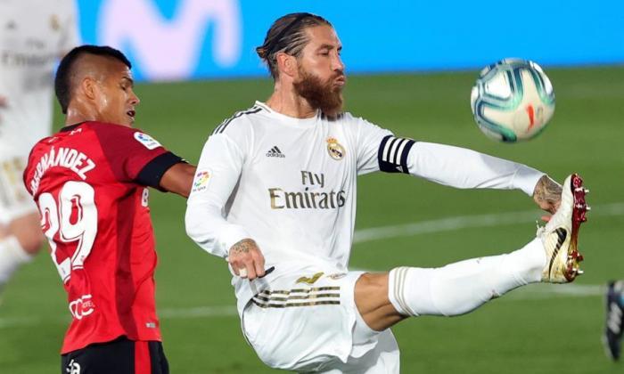 Juan Camilo Hernández tratando de ganarle una pelota a Sergio Ramos.