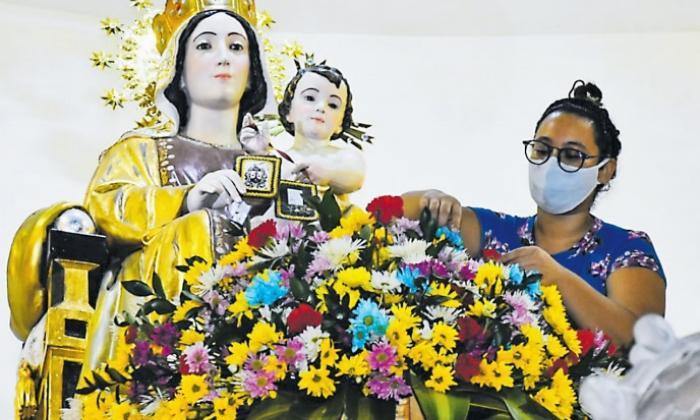 Una mujer decora la imagen de la virgen en la iglesia Nuestra Señora del Carmen en B/quilla.