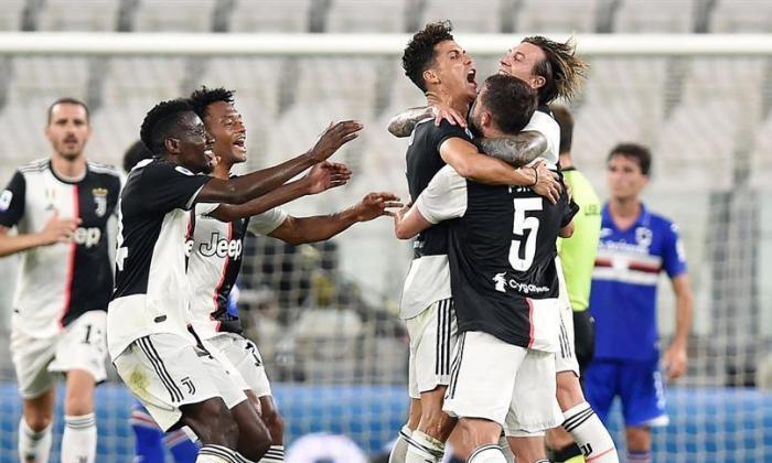Varios jugadores de Juventus, entre ellos Cuadrado, corren a felicitar y abrazar a Cristiano Ronaldo por abrir el marcador.