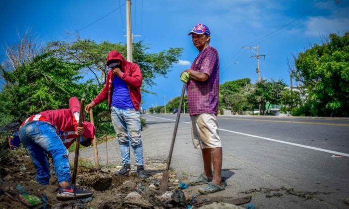Varios hombres trabajan a un costado de la vía.