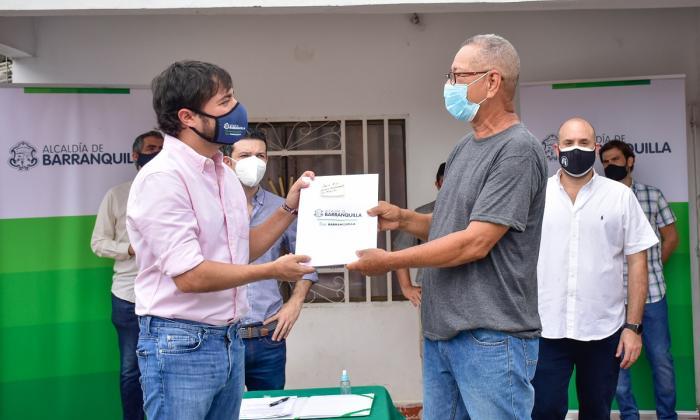 El alcalde entrega el título de propiedad a uno de los primeros beneficiados en el barrio 7 de Abril.