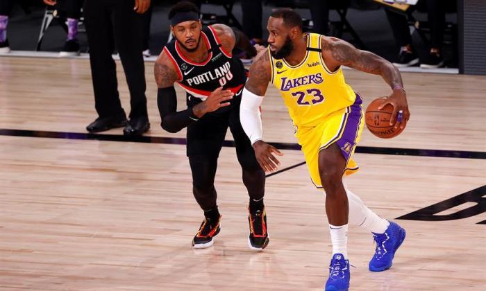 LeBron James y Carmelo Anthony disputan cara a cara una jugada.