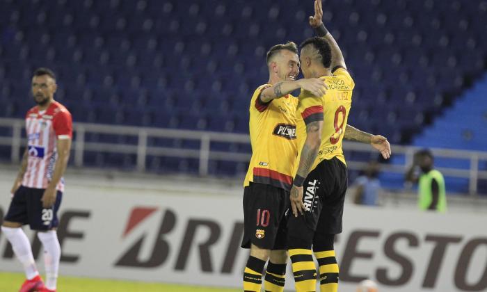 Jonatan 'el Loco' Álvez celebrando su gol con Damián Díaz, mientras Piedrahíta, al fondo, muestra su desazón.