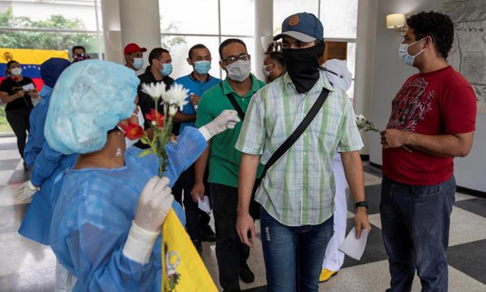 Trabajadores sanitarios despiden a un grupo de personas que se recuperaron del COVID-19 en un hotel sanitario  en Caracas.