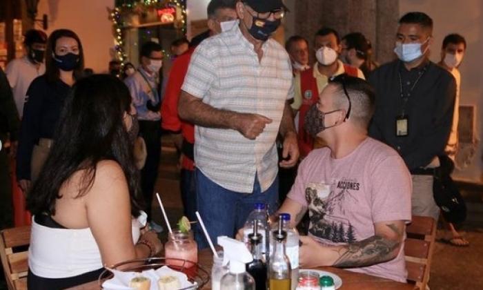 El alcalde William Dau habla con dos comensales en un restaurante del Centro Histórico de Cartagena.