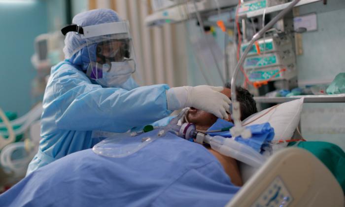 Un médico atiende a un hombre que se encuentra hospitalizado en una unidad de cuidados intensivos.