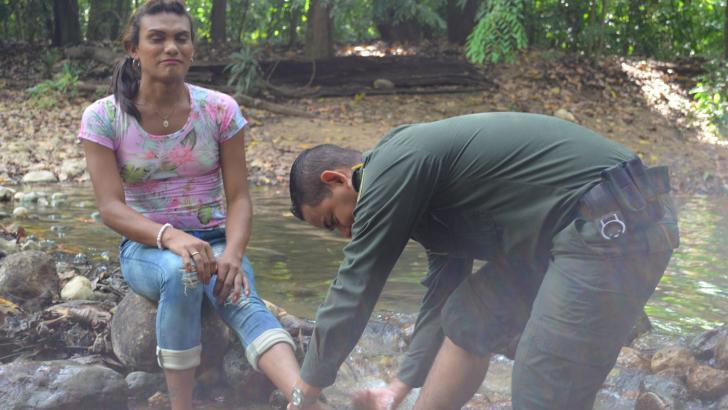 El agente de Policía, José Lara, lava los pies de Mayalín Márquez, víctima de violación.