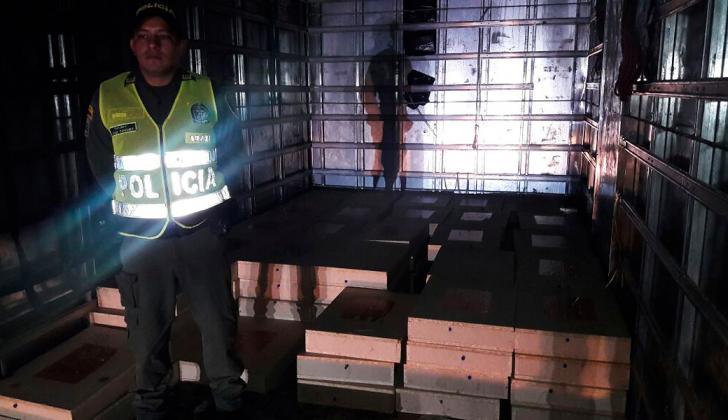 Un policía custodia las 101 cajas con monedas de 500 pesos.