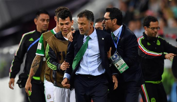 Osorio es sujetado por integrantes del cuerp técnico y jugadores de la selección de México.