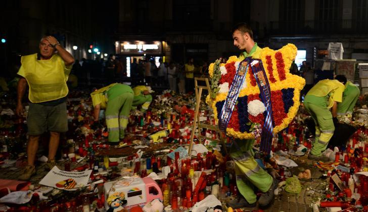 Los trabajadores municipales retiran flores de un homenaje en memoria de las víctimas en Ramblas.