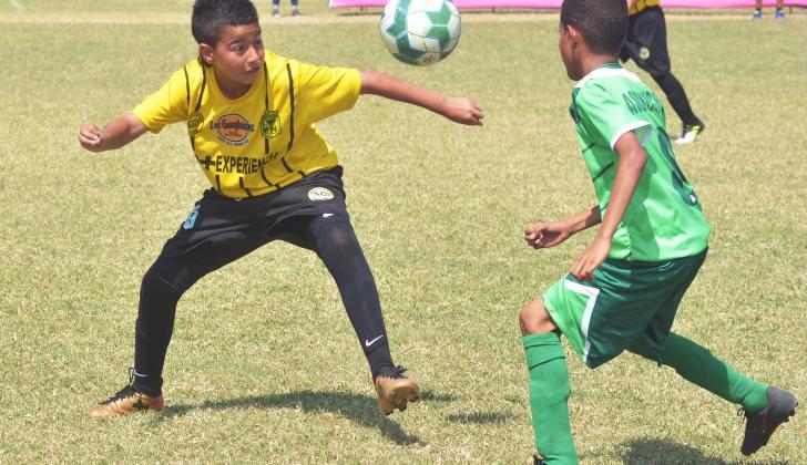 Martín Elías Díaz Jr (i) intenta despejar el esférico.