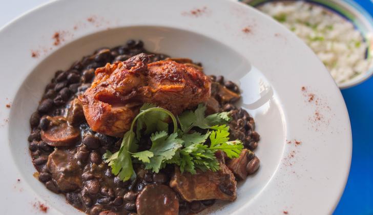 En el plato típico brasilero, el cerdo es la fuerza y los frijoles la base de un golpe de sabores completos y contundentes.