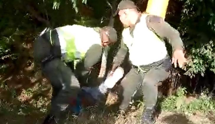 Momento en que los policías sacan el cuerpo del motorizado del sector enmontado donde cayó.
