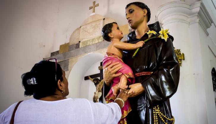 """Una feligrés agarra la mano del San Antonio recién """"restaurado""""."""