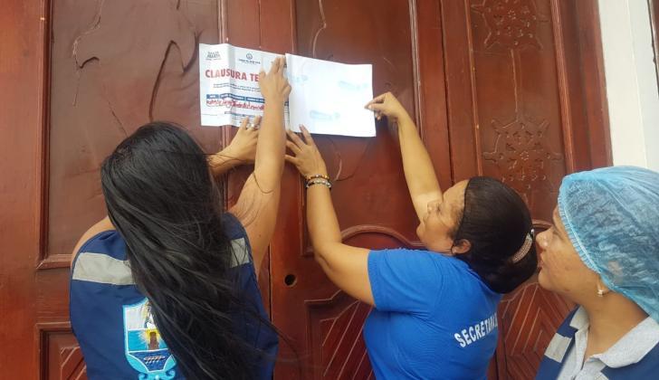 Funcionarias de la Secretaría de Salud de Santa Marta al momento de colocar los sellos.