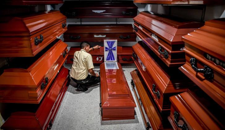 Trabajador revisa un ataúd en una funeraria.