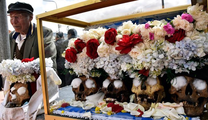 La gente llega al cementerio con sus cráneos.