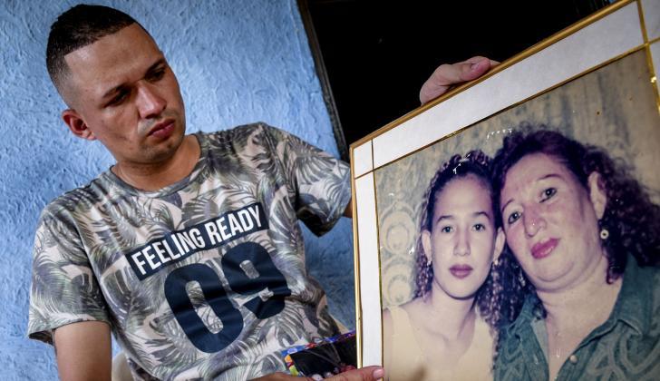 Erick Ramos sostiene un cuadro donde aparece Madeleyn junto a su madre.