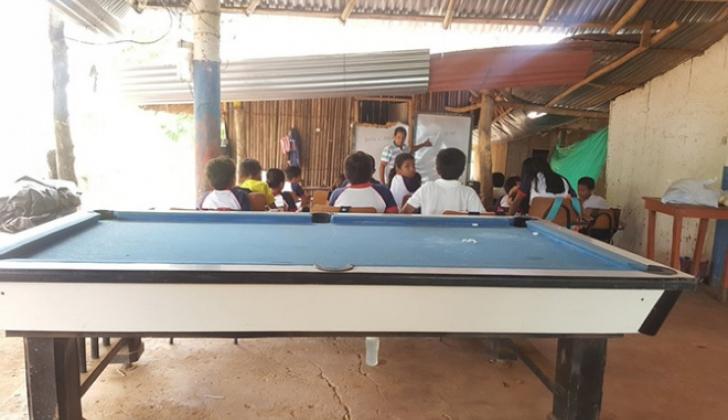 Una mesa de billar en primer plano y un grupo de los pequeños alumnos en la hora de clase.