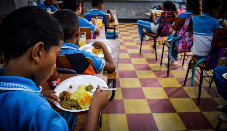 Por la falta de espacio, los estudiantes tienen que almorzar en sus salones de clase, sobre los escritorios.