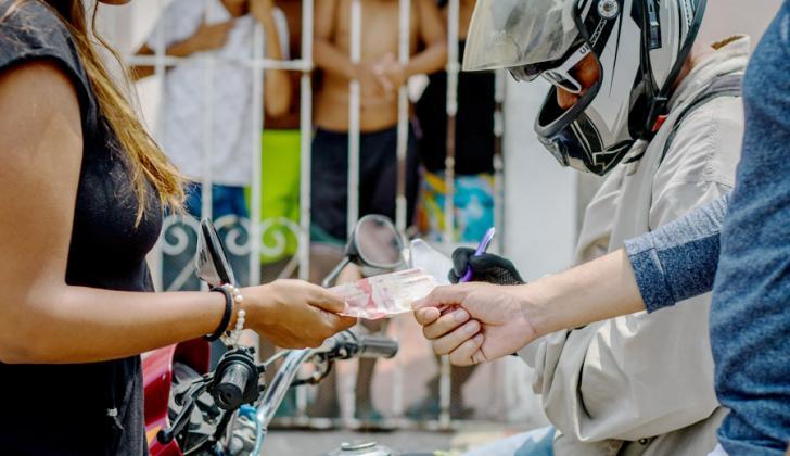 Imagen que ilustra el momento del pago de una deuda en un barrio popular de Barranquilla.