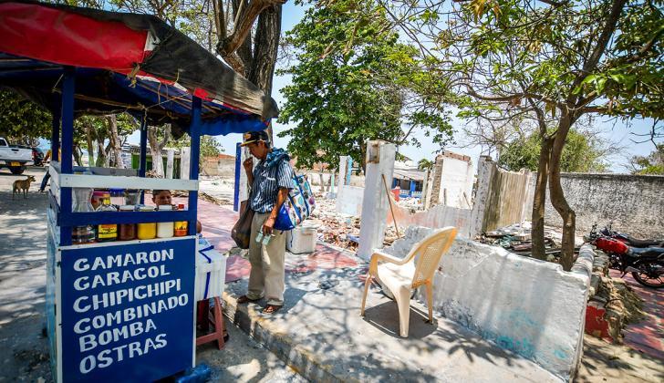 Un vendedor ofrece sus productos cerca de los predios que han sido demolidos.