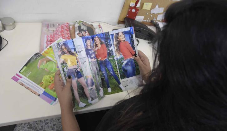Una cliente de un vendedor por venta directa observa varios catálogos.