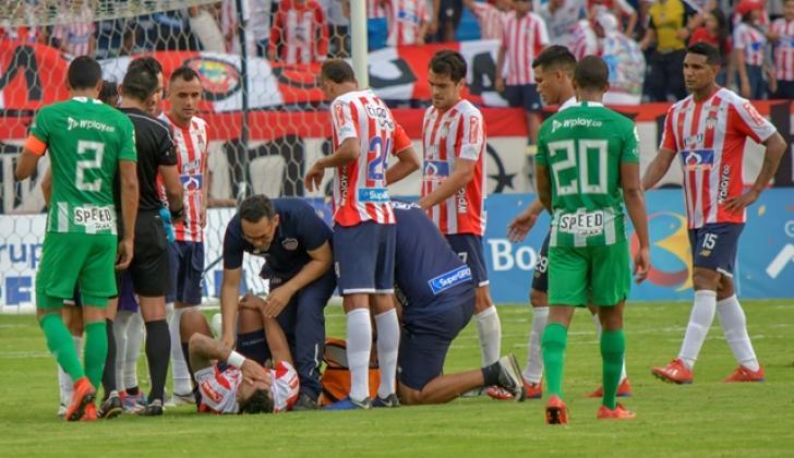 Momento en el que el defensor barranquillero Jefferson Gómez es atendido por el médico del Junior en el duelo ante Nacional.