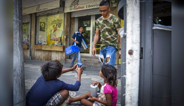 Dos niños piden dinero a un transeúnte en las calles del Paseo Bolívar.