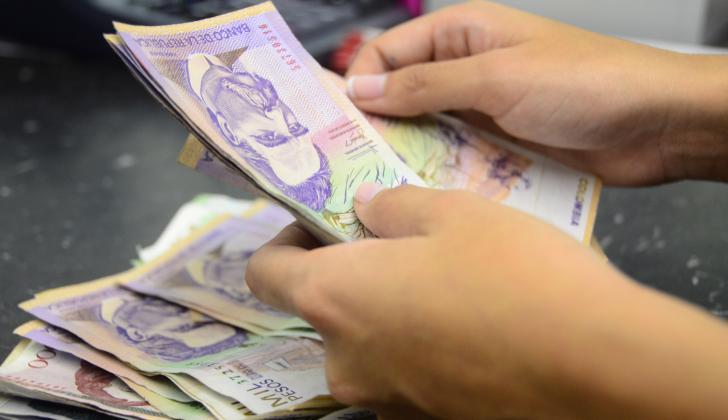 Una trabajadora barranquillera cuenta billetes de alta denominación.